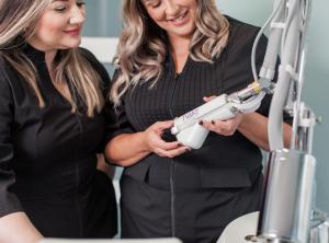 Sarah and Natalie operating laser machine