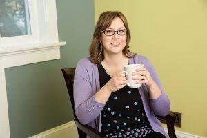 Tina Hall sitting in chair holding coffee mug