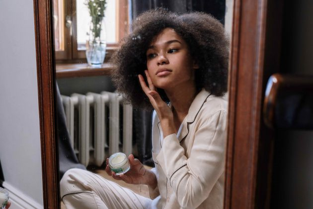 Model sitting in front of mirror applying skincare to face